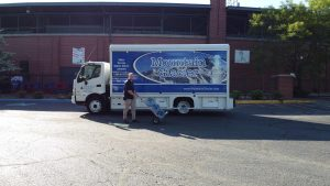 A Mountain Glacier water delivery truck. A deliver person stands outside using a hand truck to deliver a 5-gallon jug of water.