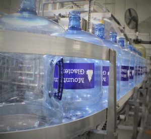 Five-gallon jugs of distilled water move along a conveyor in a processing facility.