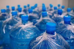 A row of large bottles of drinking water for a cooler. Water delivery.