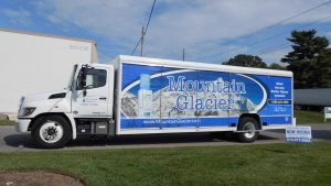 A Mountain Glacier water delivery truck parked outside a commercial building.
